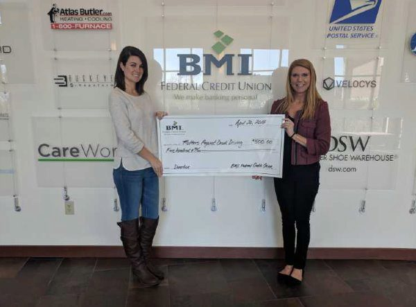 bmi fcu charitable giving director presenting a check to charity