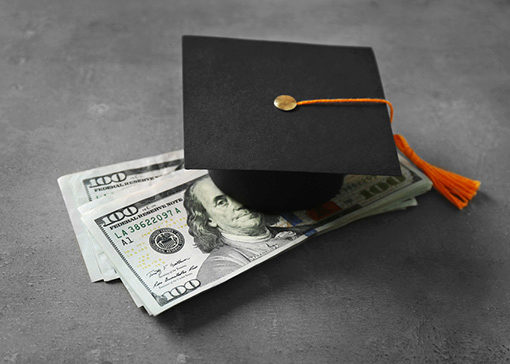 cap and diploma with bills