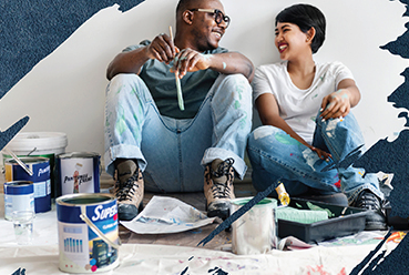couple smiling on the floor with paint supplies