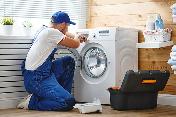 man repairing a washer and dryer