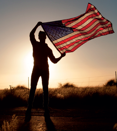 military guy with flag at sunset