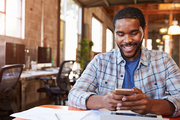 man smiling looking at phone in cafe