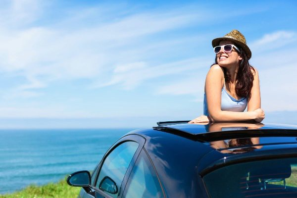 woman standing in car with sun roof