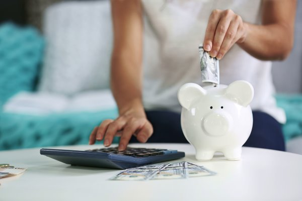 woman with calculator putting money in a piggy bank